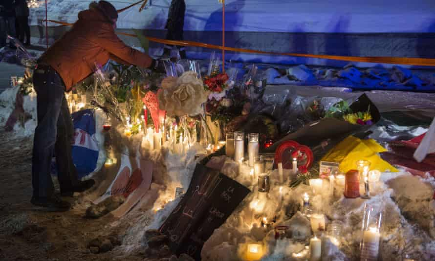 A man places a candle during a vigil in Quebec City on 30 January 2017 after a gunman shot and killed several people there.