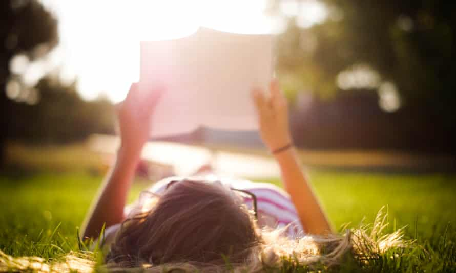 A woman reading a book lying on her back in sunlight
