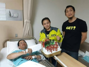 A Grab bike driver, who also works for GET, is visited by Get staff workers in hospital after he was beaten by a motorcycle taxi group in Sukhumvit 33 area.