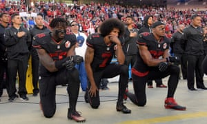 San Francisco 49ers outside linebacker Eli Harold (58), quarterback Colin Kaepernick (7) and free safety Eric Reid (35) kneel in protest during the playing of the national anthem before a NFL game against the Arizona Cardinals in Santa Clara, California, 6 Oct. 2016.