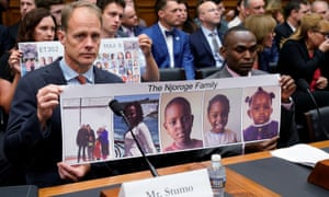 Michael Stumo and Paul Njoroge, right, hold a photo of Njoroge's family members during a congressional hearing in Washington DC.