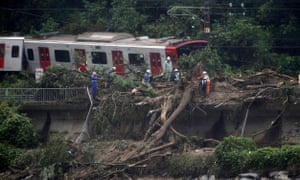 An emergency crew works on a train derailed due to landslides caused by heavy rain in Karatsu city, Saga prefecture.