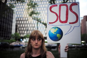 "A woman displays a placard during a demonstration in New York on June 1, 2017, to protest US President Donald Trump's decision to pull out of the 195-nation Paris climate accord deal. US President Donald Trump earlier announced America is ""getting out"" of a deal he said imposed ""draconian"" burdens that would cost the US millions of jobs and billions in cold hard cash. / AFP PHOTO / Jewel SAMADJEWEL SAMAD/AFP/Getty Images"