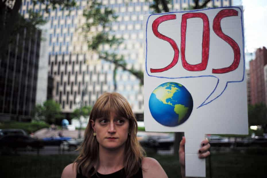 """A woman displays a placard during a demonstration in New York on June 1, 2017, to protest US President Donald Trump's decision to pull out of the 195-nation Paris climate accord deal. US President Donald Trump earlier announced America is """"getting out"""" of a deal he said imposed """"draconian"""" burdens that would cost the US millions of jobs and billions in cold hard cash. / AFP PHOTO / Jewel SAMADJEWEL SAMAD/AFP/Getty Images"""