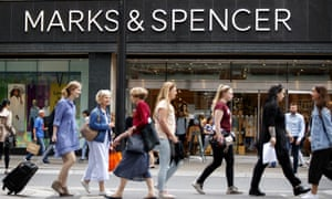Shoppers walk past a Marks & Spencer shop on Oxford Street in central London.