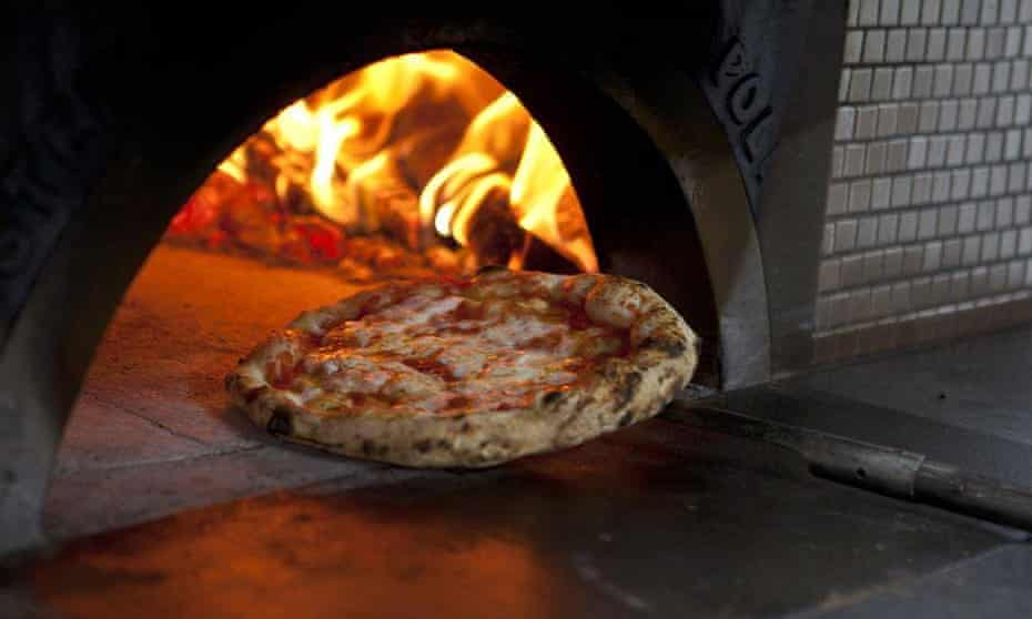 Pizza perfection emerging from Franco Pepe's wood-fired pizza oven