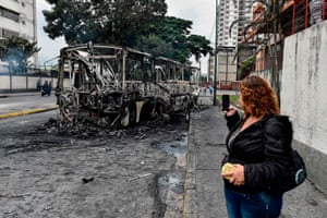 A woman takes a picture of a burned bus, that was set up on fire in Caracas on the eve of a march called by Venezuelan opposition on the anniversary of 1958 uprising that overthrew military dictatorship