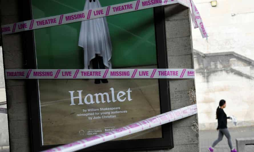 """A tape with the inscription """"Missing live theatre"""" is wrapped around a pillar outside the National Theatre in London, following the coronavirus outbreak"""