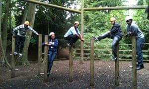 Six people posing on an outdoor assault course
