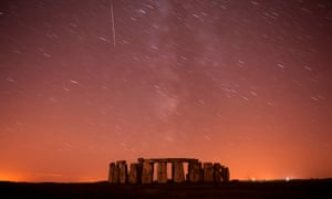 A meteor streaks past stars in the night sky over Stonehenge in Salisbury Plain, southern England.