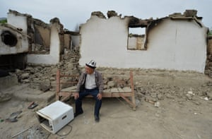 Kok-Terek, Kyrgyzstan. A man sits in front of a destroyed house in the village of Kok-Terek. People were evacuated from their villages following recent clashes at the Tajik-Kyrgyz border over disputed water tanks