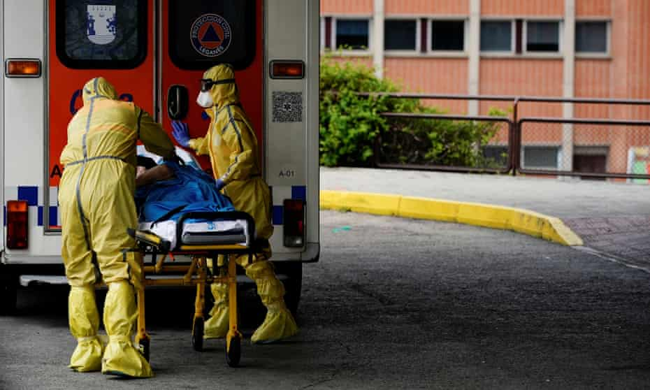 Healthcare workers push a patient on a stretcher at a hospital in Leganes, near Madrid, Spain
