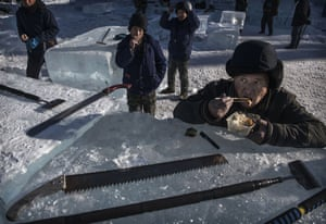 A block of ice serves as a lunch table for a hungry worker