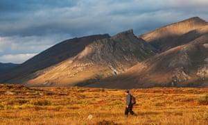 A man in a hat walking near mountain peaks