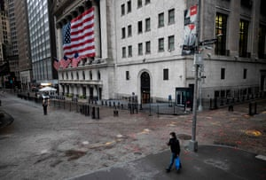 A man wearing a mask walks pass the New York Stock Exchange (NYSE) on April 30, 2020 in New York City.