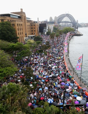 People put up their umbrellas as the rain starts to set in along the harbour foreshore near Circular Quay