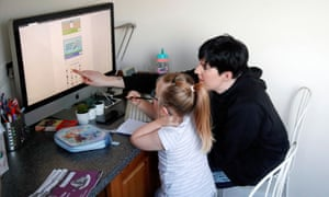 Charlotte Rose assists one of her children, who is home schooled in Milton Keynes, Britain, January 5, 2021.