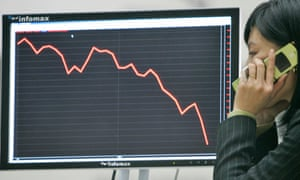 a South Korean businesswoman stands by a black and red screen graph charting a heavy downward trend