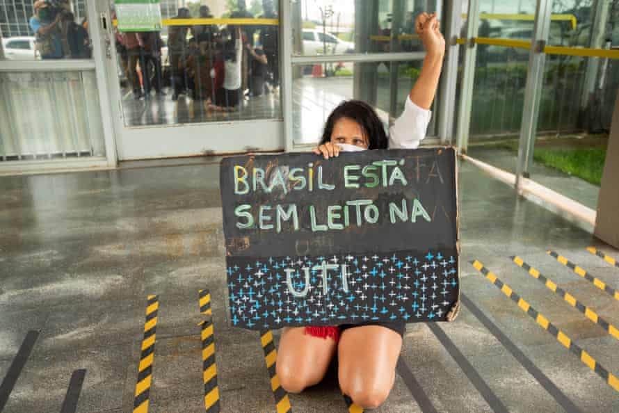 """A woman holds a poster that reads """"Brazil does not have a bed in the ICU"""" as she kneels in front of the Ministry of Health in Brasilia, Brazil."""