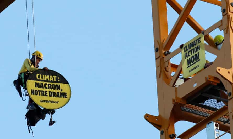A Greenpeace activist holds a sign reading 'Climate: Macron, our drama' while dangling from a crane near Notre Dame Cathedral in Paris