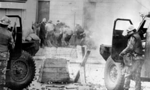 Soldiers taking cover behind their sandbagged armoured cars while dispersing rioters with CS gas during protests in Derry in 1972.