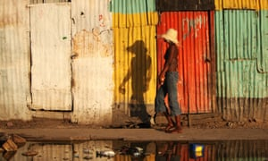 A woman walks by colorful old houses in Haiti.