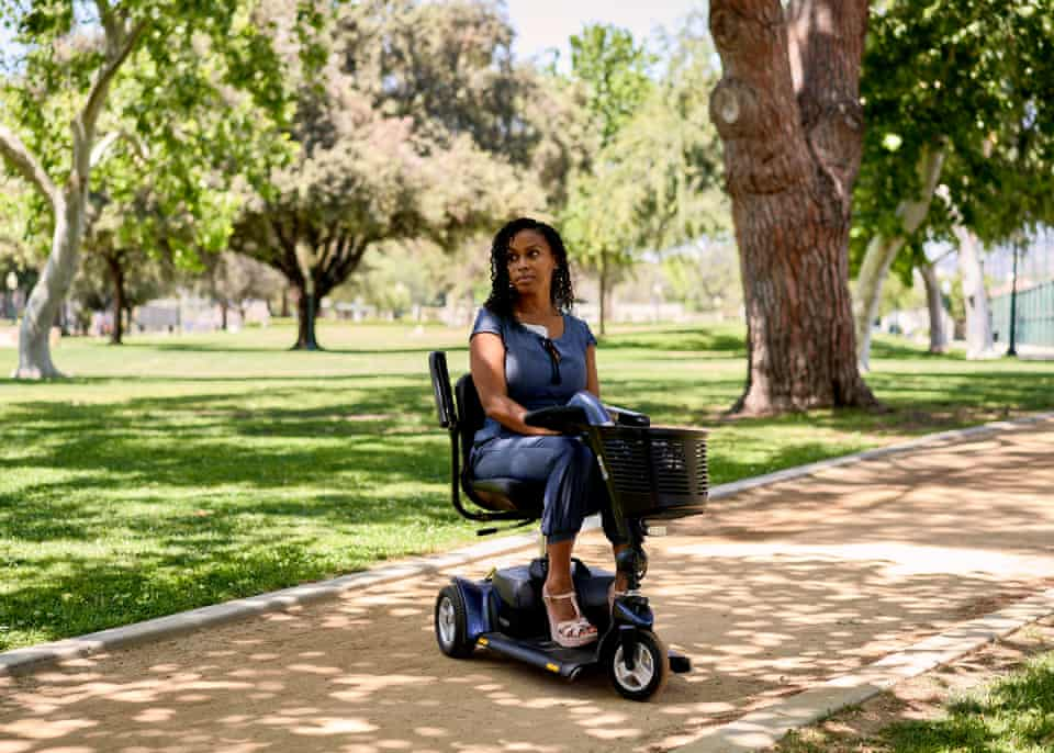 Ashanti Daniel, 40, a former nurse, poses for a portrait on her scooter at a park in Beverly Hills.