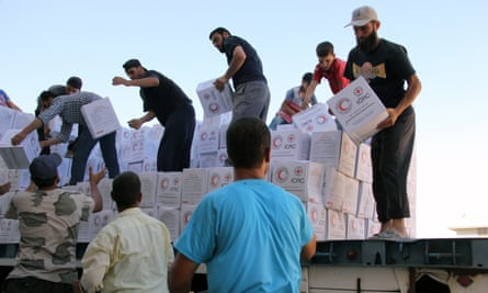 Syrians unload boxes after a 48-truck convoy from the ICRC, SARC and UN entered the Syrian rebel-held town of Talbiseh.