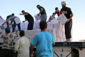 Syrians unload boxes after a 48-truck aid convoy entered the rebel-held town of Talbiseh, a besieged area in northern rural Homs, in July.