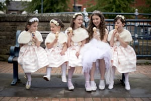Stalybridge, EnglandA group of girls enjoy ice creams while attending the annual Whit Walks. Local churches continue to parade on Whit Sunday. Typically, the parades include brass bands, and girls attending are dressed in white.