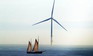 A sailing ship passes a wind turbine