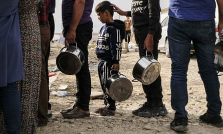 Syrian refugees wait to receive bread and water at the Bardarash camp in Dohuk, Iraq