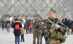 French military officers stand guard before the New Year's Eve celebrations at the Louvre.