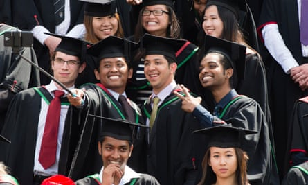 Overseas students in traditional gowns and mortar boards take a selfie on graduation day at Aberystwyth University