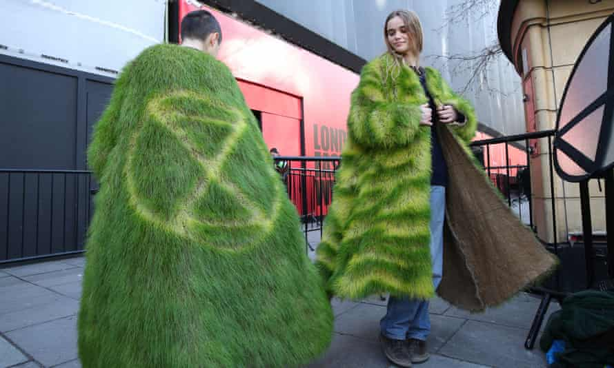 Climate change activists model 'grass' coats during an Extinction Rebellion protest outside a London fashion week event