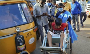 A young patient is brought in a wheelchair to the district government hospital in Eluru, Andhra Pradesh state, India, Sunday, 6 December 2020.