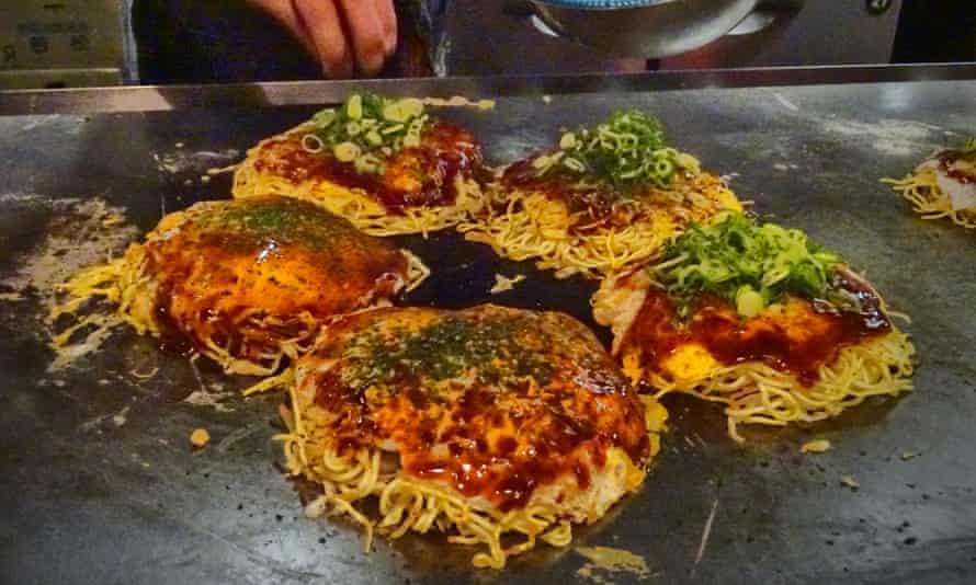 Okonomiyaki get their final garnish at a restaurant near Hiroshima, Japan.