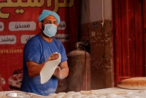 A Palestinian baker wearing a protective mask prepares the dough for fresh bread at a bakery in Gaza City during lockdown in the Palestinian enclave due to increasing cases of coronavirus infections.