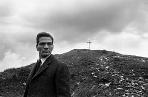 Pier Paolo Pasolini in front of a hill topped by a cross