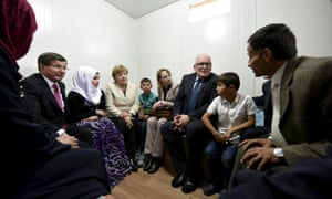 Angela Merkel, Ahmet Davutoğlu and Frans Timmermans speak to a refugee family