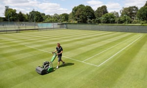 Head groundsman Paul Bishop cuts the grass on the courts at St George's Hill Lawn Tennis Club in Weybridge as they prepare to reopen.