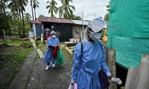 Health workers walk on a street during a day of sampling of Covid-19 quick tests in Juanchaco beach, Colombia.
