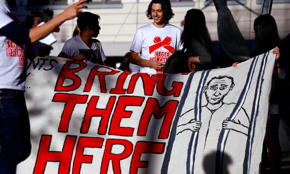 Protesters with a 'bring them here' sign