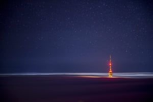 A television transmission tower is photographed above a huge cloud of fog in Pecs, Hungary