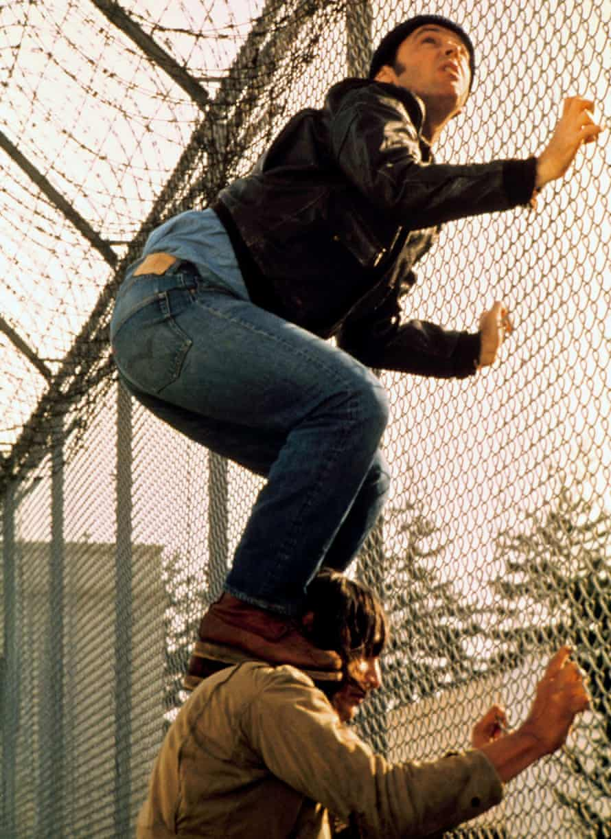 Jack Nicholson standing on the shoulders of Will Sampson, both grabbing a chain-link fence, in One Flew Over the Cuckoo's Nest