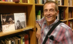 John Evans in bookshop, with copy of Journeying Boy