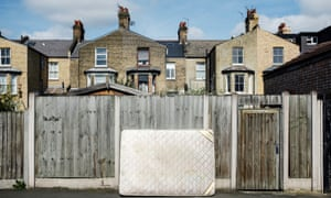 Abandoned mattress by a wooden fence on a city street, London, UK