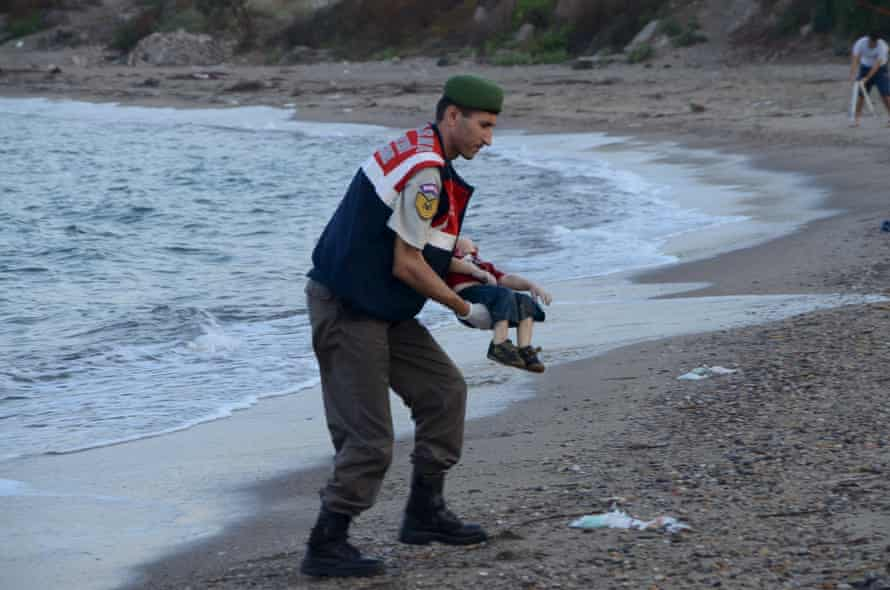 A Turkish gendarmerie carries a young migrant, who drowned in a failed attempt to sail to the Greek island of Kos, in the coastal town of Bodrum, Turkey