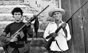 An 87-year-old veteran of the first Sandino rebellion stands with an 18-year-old Sandinista guerrilla holding an assault rifle in Leon, Nicaragua, June 19, 1979.