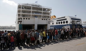 Refugees, mostly from Syria, line up as they wait for a bus after disembarking from a ferry at the port of Piraeus, near Athens
